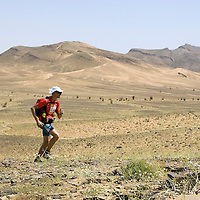 25 March 2007: Runner #320 Nicolas Margarot of France runs across a blooming desert because of a rainy winter between Irhs and Khermou during the first stage of  the 22nd Marathon des Sables, a 6 days and 151 miles endurance race with food self sufficiency across the Sahara Desert in Morocco. Each participant must carry his, or her, own backpack containing food, sleeping gear and other material.