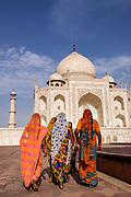 A group of women wearing colourful saris visiting the iconic, ivory-white marble mausoleum, Taj Mahal, Agra, India