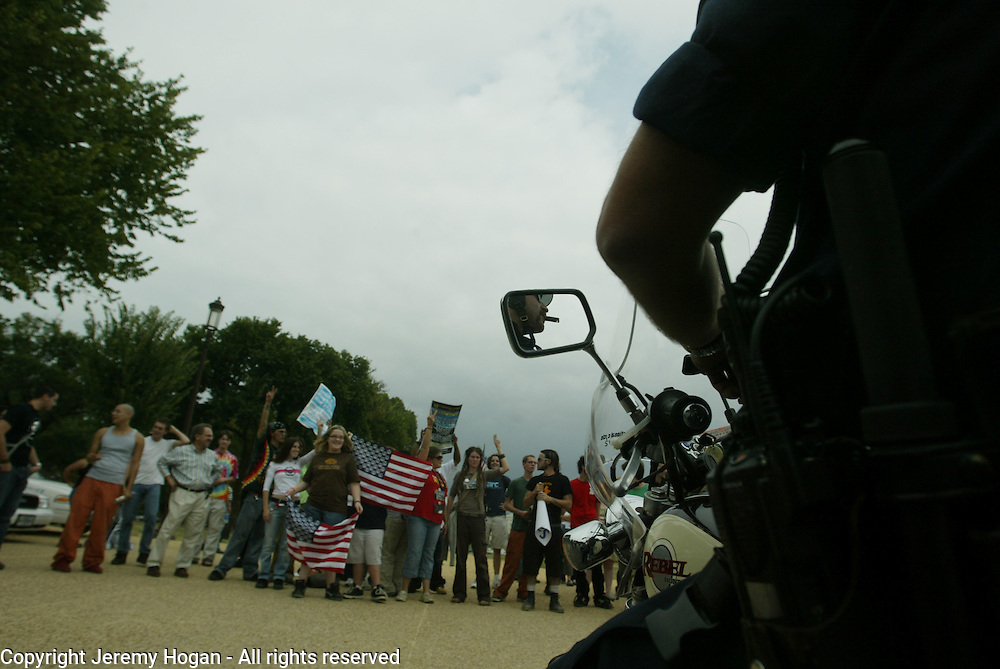 A police officer smokes a cigar while keeping an eye on anti-war protesters who has shown up at a support our troops rally at the National Mall.