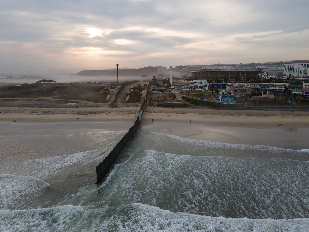 Waves in the sea at the border wall between San Diego, California on the left, and Tijuana, Mexico on the right.