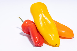 Group of sweet peppers, one red, one yellow, one orange on white background