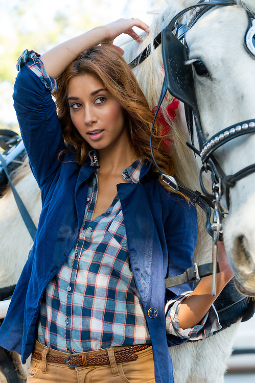 Beautiful sultry woman with long brunette hair standing alongside a horse looking away from camera.