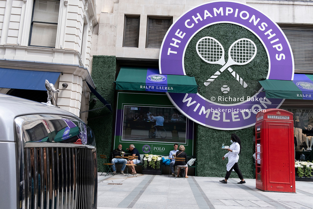The logo for the Lawn Tennis Association's (LTA) Wimbledon tennis championship is reflected in the polished chrome of a Rolls-Royce, outside style retailer, Ralph Lauren in Bond Street, on 8th July 2021, in London, England.