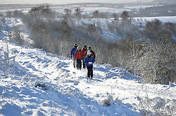 © Licensed to London News Pictures. 15/01/2016. North Yorkshire Moors, UK. Walkers take a path through the snow at the Hole of Horcum on the North Yorkshire Moors. Photo credit : Anna Gowthorpe/LNP