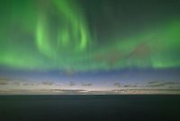 The northern lights shine through evening twilight over the Atlantic Ocean near Ólafsvík, Iceland.
