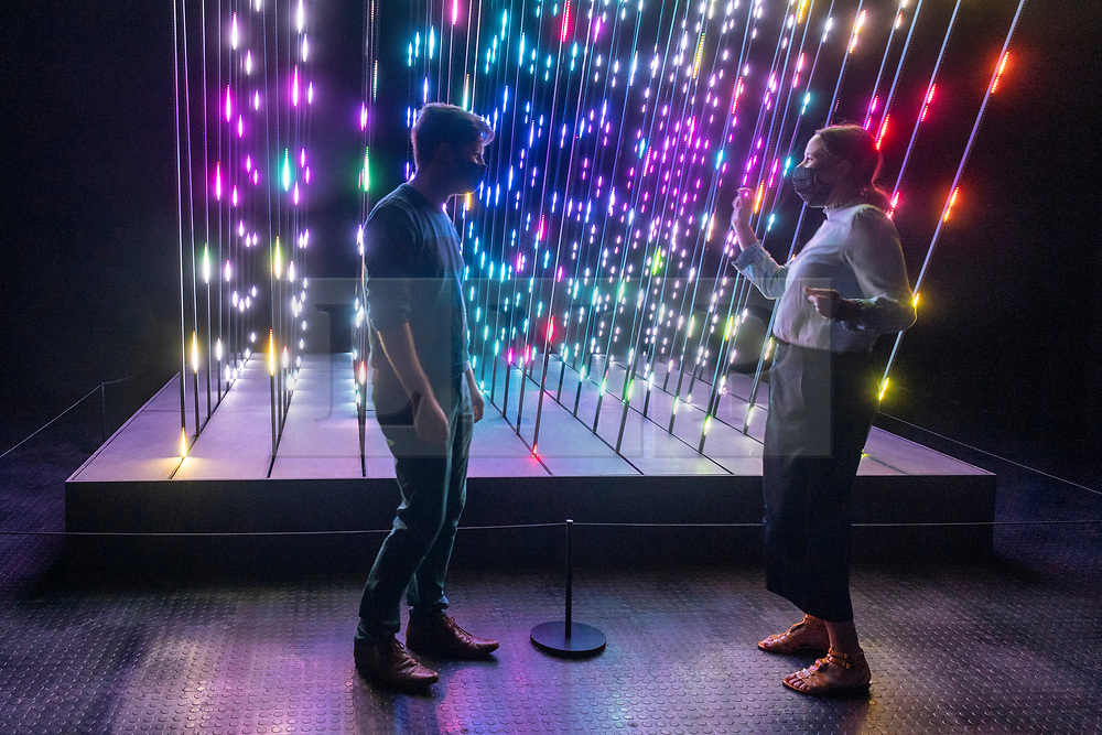 © Licensed to London News Pictures. 28/07/2020. London, UK. Design Museum staff members dance in front of a light and sound installation titled CORE, 2019, by 1024 Architecture on display at The Design Museum exhibition 'Electronic: From Kraftwerk to The Chemical Brothers'. The exhibition explores the hypnotic world of electronic music and discovers its global impact from underground movements to the mainstream  and features appearances from the likes of Jeff Mills, Ellen Allien, Jean-Michel Jarre and more. It will also feature a 3-D experience surrounding electronic pioneers Kraftwerk, with the installation soundtracked by legendary DJ and producer, Laurent Garnier. Photo credit: Ray Tang/LNP