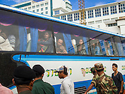 16 JUNE 2014 - POIPET, CAMBODIA:  A bus bringing Cambodian migrants back to Cambodia arrives in Poipet, Cambodia. More than 150,000 Cambodian migrant workers and their families have left Thailand since June 12. The exodus started when rumors circulated in the Cambodian migrant community that the Thai junta was going to crack down on undocumented workers. About 40,000 Cambodians were expected to return to Cambodia today. The mass exodus has stressed resources on both sides of the Thai/Cambodian border. The Cambodian town of Poipet has been over run with returning migrants. On the Thai side, in Aranyaprathet, the bus and train station has been flooded with Cambodians taking all of their possessions back to Cambodia.   PHOTO BY JACK KURTZ