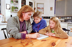 Mother sitting at kitchen table with young children writing notes,
