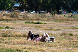 """© Licensed to London News Pictures. 13/09/2020. London, UK. Sunbathers enjoy the sunshine in a packed Wimbledon Common  in South West London this afternoon a day before the """"Rule of 6"""" comes into force on Monday as weather experts announce a 5 day mini-heatwave in the South East of England this week with highs of 29c. Prime Minister Boris Johnson announced on Friday that gatherings of more than six people will be banned from Monday (tomorrow) in the hope of reducing the coronavirus R number. The Rule of Six as it is known, has already become unpopular with MPs and large families for being too strict. Photo credit: Alex Lentati/LNP"""