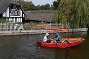 Two boating enthusiasts row past typical Norfolk Broads architecture at Hickling Broad, on 11th August 2020, in Hickling, Norfolk, England.