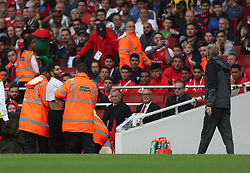 29 July 2017 London : Emirates Cup - Arsenal v Benfica - a pitch invading fan is escorted away, close to Arsene Wenger.<br /> Photo: Mark Leech