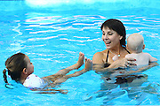 Grandmother with grandchildren in a swimming pool Model release available