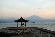 Lone figure in beachside pagoda, with Bali's sacred mountain, Gunung Agung, in background, viewed from Sanur beach at sunrise. Sanur, Bali, Indonesia.