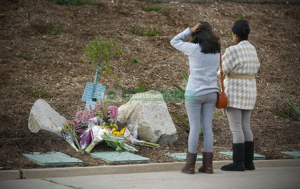 May 6, 2017 - San Diego, CA, USA - A mother and her daughter pay their respects at a memorial of flowers that is starting to grow in front of Torrey Pines High School near where a 15-year-old 9th grader at the school was shot and killed by San Diego Police officers early Saturday morning, May 6, 2017. Police believe the boy called police, and when they arrived pointed a gun at them and didn't follow their commands to drop it. It turns out that the gun is a semi-automatic BB air pistol. (Credit Image: © Howard Lipin/TNS via ZUMA Wire)