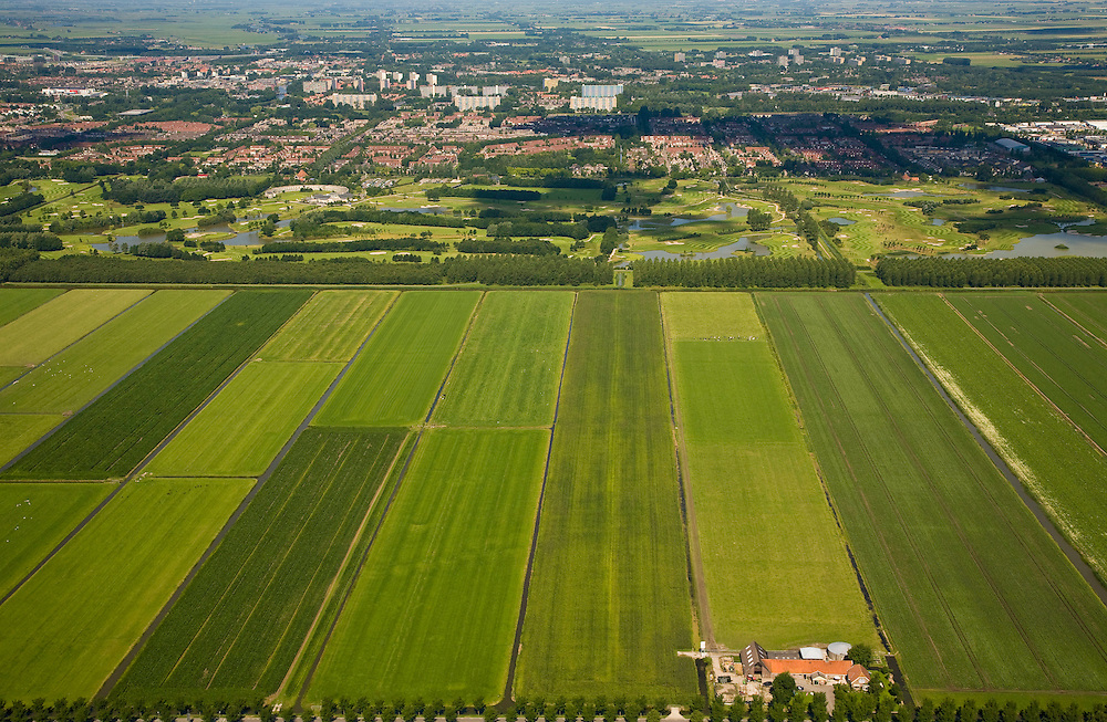 Nederland, Noord-Holland, Purmer, 14-07-2008; Oostelijk deel van de polder is nog ongerept, met boerderij aan de Oosterweg; maar de verrommeling slaat toe: het aangelegde (!) Purmerbos, met golfterrein en en in de verdere achtergrond de meest recente stadsuitbreiding, de woonwijken Purmer-Noord en Purmer-Zuid (links); daar achter de hoogbouw en flats van de wijk Wheermolen. .luchtfoto (toeslag); aerial photo (additional fee required); .foto Siebe Swart / photo Siebe Swart