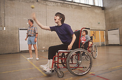 Young girl with disability; who is wheelchair user; taking part in ball game in sports hall,