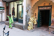 A traditionally dressed woman walks past a modern upscale shop in the trendy village of Sharpur Jat now home to expensive couture and the burgeoning fashion industry. New Delhi, India