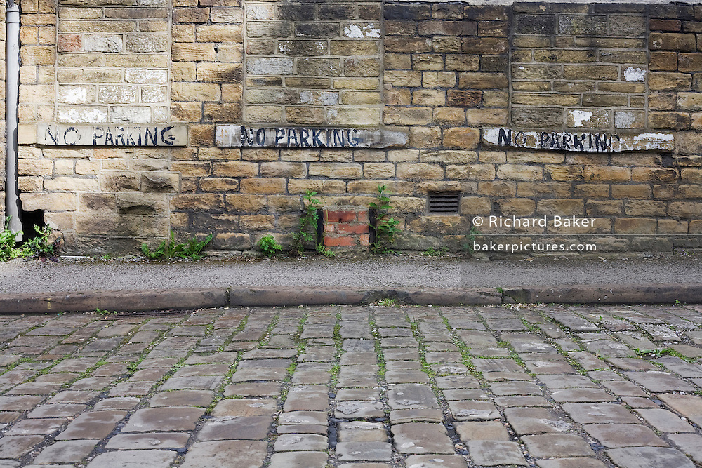 The words No Parking has been written in pain by hand three times on the sills of now bricked-up windows in a quiet cobbled street near Bradford city centre, Yorkshire.