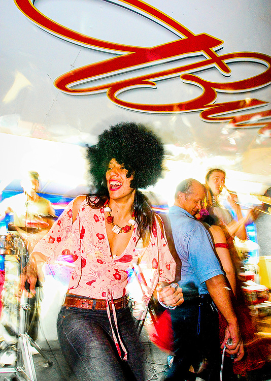 Wearing Afro wig, Norelkys Blazekovic dances to salsa beat band The Spam Allstars at an art carnival on 36th Street in Miami during Art Basel Miami Beach 2003