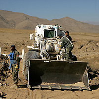 Fully armoured mechanical diggers with 'mine proofed' tires are used to clear ground. Afghanistan remains one of the most heavily mined countries in the world. A mine clearance team from the Halo Trust have been working for more than a year in the small village of Kohe Safi and have removed 800 mines and 118 unexploded bombs. Kohe Safi, Afghanistan on the 1st of November 2007..Throughout the country the Halo Trust alone is working to clear 90 million square meters of mine fields containing some 640,000 mines, they estimate it will take them 18 years to complete this task..A break through in mine detection not seen since  World War II is due to speed things up in the coming year when Halo become the first civilian organisation to use H-STAMIDS (The Handheld Stand-Off Mine Detection System) a new combination tool with a metal detector and ground penetrating radar system. The H-STAMIDS remain classified and during recent trails in Afghanistan the device had to be returned to the US military at the end of each day. The new equipment should make mine clearance 2-3 times faster.