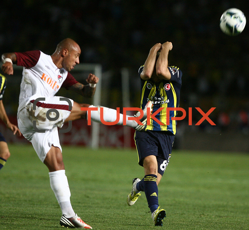 S.B. Elazigspor's and Fenerbahce's players in action with ball ,Caner Erkin closing his face for keeping Elazigspor's player stroke during their Turkish superleague soccer match S.B. Elazigspor between Fenerbahce at the Ataturk stadium in izmir Turkey on Saturday 18 August 2012. Photo by TURKPIX