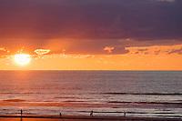 people walking along beach at sunset