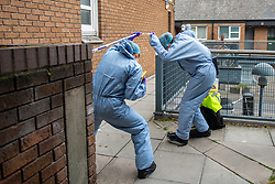 © Licensed to London News Pictures. 04/07/2020. London, UK. Forensic investigators pass under police tape as they search for evidence at a block of flats on Westbourne Estate in Islington. Metropolitan Police Service officers were called at 15:20BST on Saturday, 4 July to Roman Way N7 following reports of shots fired. Officers attended with London Ambulance Service (LAS) and found a man, believed to be aged in his early 20s, suffering from gunshot injuries. Despite their best efforts, he was pronounced dead at the scene. Photo credit: Peter Manning/LNP