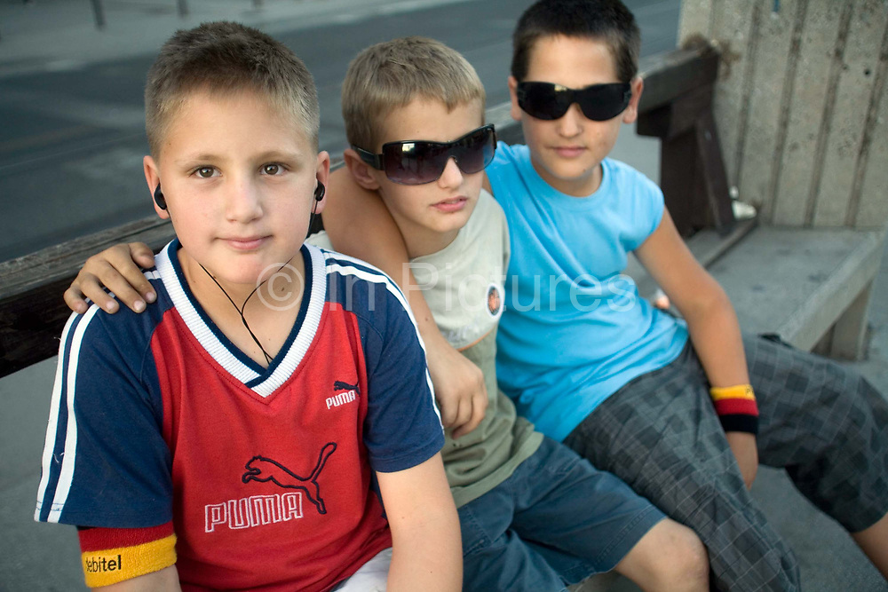 Boys, two with sunglasses and one with a personal stereo, sit on a bench in the street, Sarajevo, Bosnia