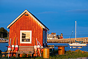 A red fish house against the blue sky during sunset at Orrs Island, Maine. The Bailey Island Bridge, the only granite cribstone bridge is in the background.