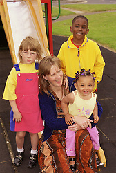 Female child minder sitting at bottom of slide in playground with multiracial group of children,