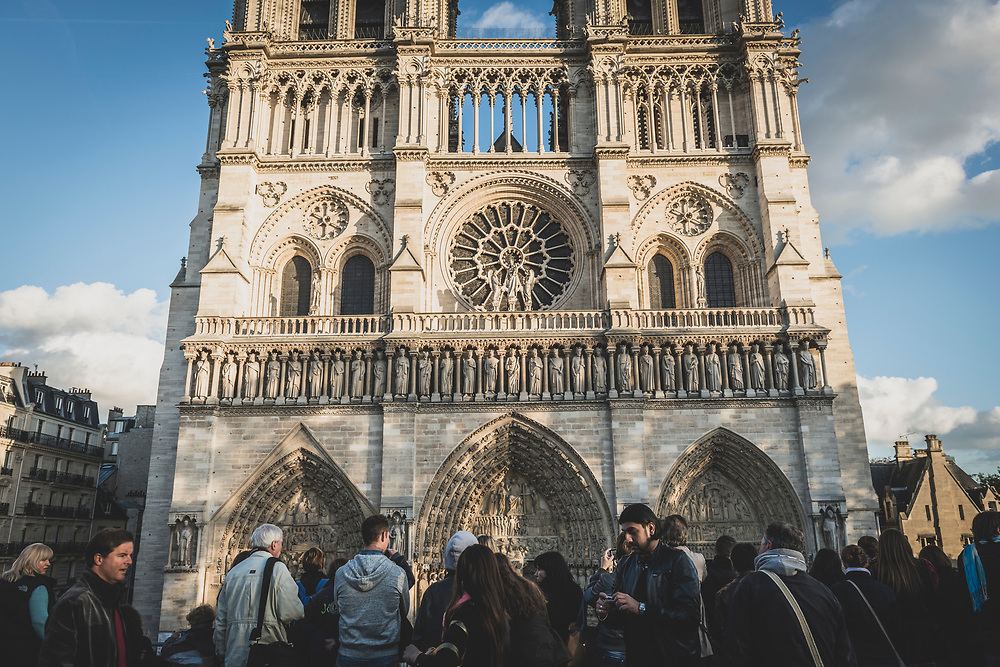 Paris, France - October 30, 2013: A crowd of people outside Notre Dame Cathedral late in the afternoon.