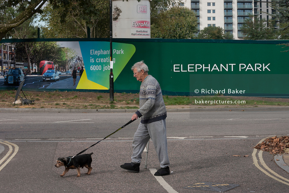 An elderly south Londoner walks his dog past a regeneration project hoarding at Elephant Park, at Elephant & Castle, London borough of Southwark. Southwark Council's development partner, Lendlease is regenerating over 28 acres across three sites at the heart of Elephant & Castle, in what is the latest major regeneration opportunity in zone 1 London. The vision for the £1.5 billion regeneration is to build on the area's strengths and vibrant character in order to re-establish Elephant & Castle as one of London's most flourishing urban quarters. The Elephant & Castle regeneration is of a scale rarely seen in central London and includes almost 3,000 new homes, plus office, retail, community, leisure and restaurant space.