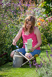 Measuring out liquid lawn feed into a watering can.