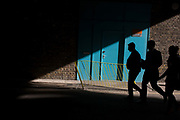 Three silhouettes walk into shadows beneath a south London railway tunnel. The three human figures make their way from strong winter sunlight into the depths of the shadow under the railway bridge tunnel in SE1, an area of businesses and apartments. A bent railing has been twisted in the direction of traffic that can drive through too.