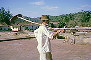 Male worker carrying shovel used for drying coffee in farmyard, Fazenda Sant' Anna, Campinas, Brazil, South America 1962