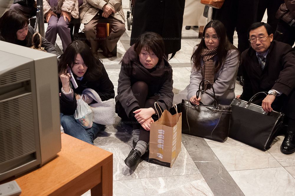 People watch TV news in the lobby of a hotel in Shibuya after a magnitude .9 earthquake hit the Tohoku region of north east Japan causing tremors in Tokyo that stopped the train and cellphone networks. Many people were stranded in the centre of Tokyo over night. Tokyo, Japan Friday March 11th 2011