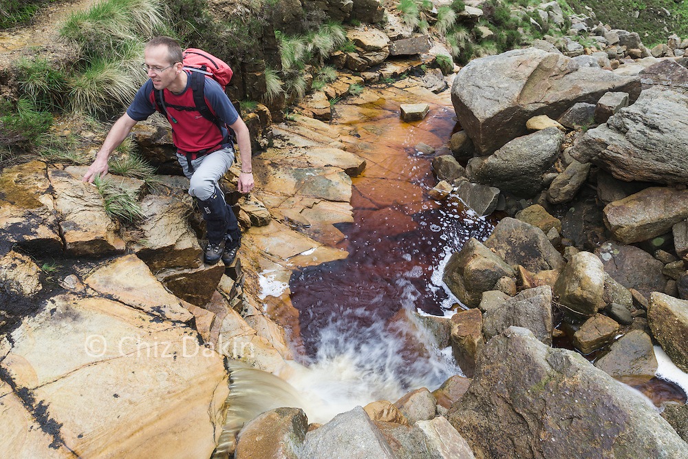Mike Hayes scrambling on drier rock to the side of a waterfall