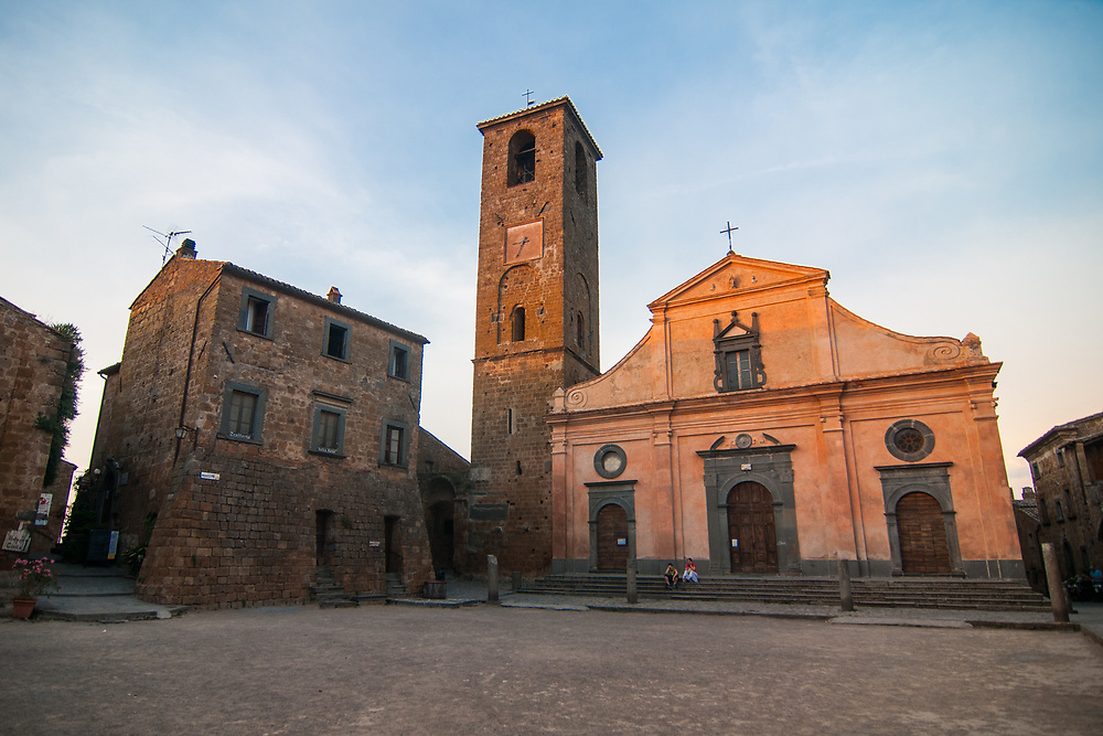 """A view of San Donato square with the church of San Donato of the village of Civita di Bagnoregio.<br /> Civita di Bagnoregio is a town in the Province of Viterbo in central Italy, a suburb of the comune of Bagnoregio, 1 kilometre (0.6 mi) east from it. It is about 120 kilometres (75 mi) north of Rome. Civita was founded by Etruscans more than 2,500 years ago. Bagnoregio continues as a small but prosperous town, while Civita became known in Italian as La città che muore (""""The Dying Town""""). Civita has only recently been experiencing a tourist revival. The population today varies from about 7 people in winter to more than 100 in summer.The town was placed on the World Monuments Fund's 2006 Watch List of the 100 Most Endangered Sites, because of threats it faces from erosion and unregulated tourism."""