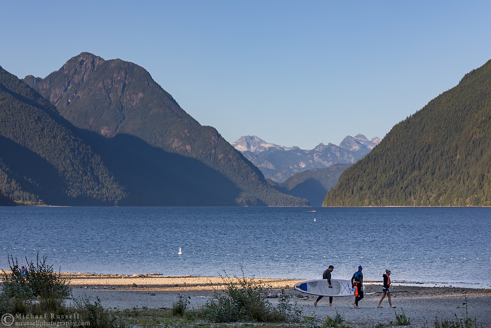 Paddleboarders walkikng across Alouette Lake South Beach at Alouette Lake in Golden Ears Provincla Park, Maple Ridge, British Columbia, Canada. The mountain peak to the north (left) is Mount Gatey and Mount Breier is in the background.