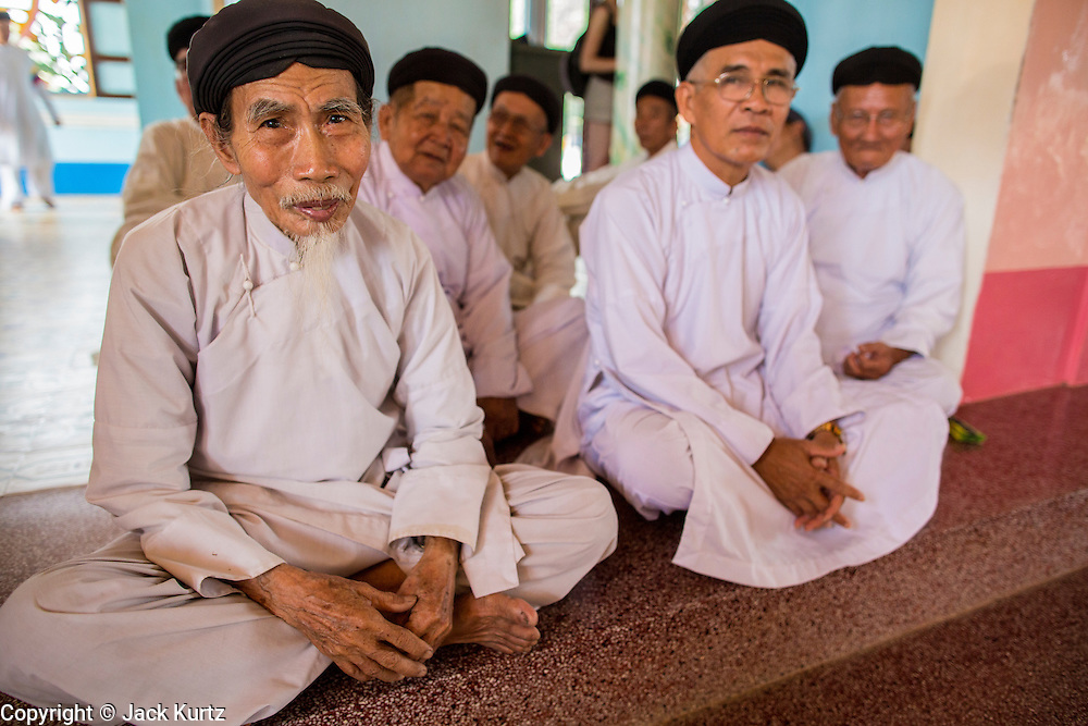 """29 MARCH 2012 - TAY NINH, VIETNAM:   Men who are members of the Cao Dai wait for noon prayer services to start at the Cao Dai Holy See in Tay Ninh, Vietnam. Cao Dai (also Caodaiism) is a syncretistic, monotheistic religion, officially established in the city of Tây Ninh, southern Vietnam in 1926. Cao means """"high"""" and """"Dai"""" means """"dais"""" (as in a platform or altar raised above the surrounding level to give prominence to the person on it). Estimates of Cao Dai adherents in Vietnam vary, but most sources give two to three million, but there may be up to six million. An additional 30,000 Vietnamese exiles, in the United States, Europe, and Australia are Cao Dai followers. During the Vietnam's wars from 1945-1975, members of Cao Dai were active in political and military struggles, both against French colonial forces and Prime Minister Ngo Dinh Diem of South Vietnam. Their opposition to the communist forces until 1975 was a factor in their repression after the fall of Saigon in 1975, when the incoming communist government proscribed the practice of Cao Dai. In 1997, the Cao Dai was granted legal recognition. Cao Dai's pantheon of saints includes such diverse figures as the Buddha, Confucius, Jesus Christ, Muhammad, Pericles, Julius Caesar, Joan of Arc, Victor Hugo, and the Chinese revolutionary leader Sun Yat-sen. These are honored at Cao Dai temples, along with ancestors.    PHOTO BY JACK KURTZ"""