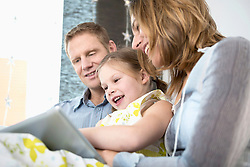 Parents with daughter sitting on couch using tablet PC