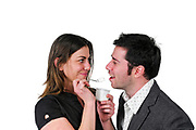 Young woman feeds her male friend a spoon of yogurt