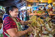 "03 OCTOBER 2012 - BANGKOK, THAILAND:   A vendor sets up stand to sell julienned papaya used in Som Tam (papaya salad), a Thai staple, in Khlong Toey Market in Bangkok. Khlong Toey (also called Khlong Toei) Market is one of the largest ""wet markets"" in Thailand. Thousands of people shop in the sprawling market for fresh fruits and vegetables as well meat, fish and poultry every day.      PHOTO BY JACK KURTZ"