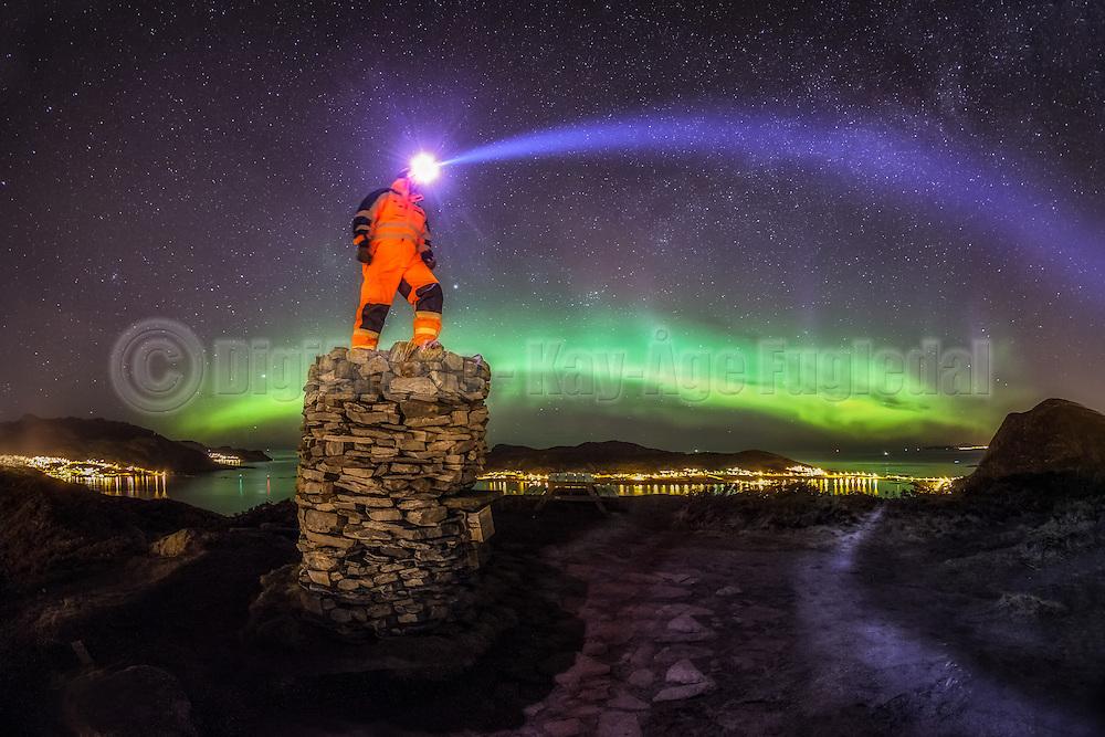 Man standing on a cairn and lights towards the sky. Perhaps he is looking for life in outer space? | En mann står på en varde og lyser ut i verdensrommet. Kanskje ser han etter livstegn? Hornseten med Remøy i bakgrunnen.