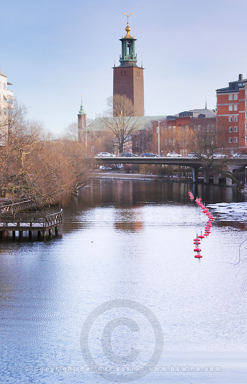Karlbergskanalen water in winter between Kungsholmen and Vasastan. A curved line of red buoys to moor boats and in the background the tower of the Stadshuset the Town Hall Stockholm, Sweden, Sverige, Europe