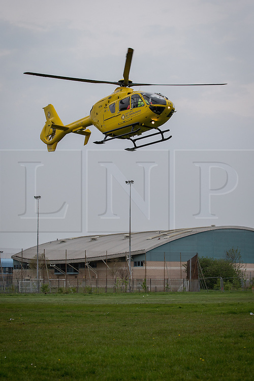 © Licensed to London News Pictures . 20/04/2014 . Manchester , UK . The North West Air Ambulance takes off from grass in Platt Fields Park in Manchester , adjacent to an Easter fun fair. A teenaged girl was struck by an 80 year old driver who fell ill behind the wheel of his car , on Chapeltown Road , in Bolton today (Sunday 20th April 2014) . The girl was transported via Air Ambulance to a ground ambulance and on to Manchester Royal Infirmary. She is reported to have suffered head injuries . Both she and the 80 year old driver (who is believed to have suffered a heart attack behind the wheel) are described as being in a serious but stable condition . Photo credit : Joel Goodman/LNP