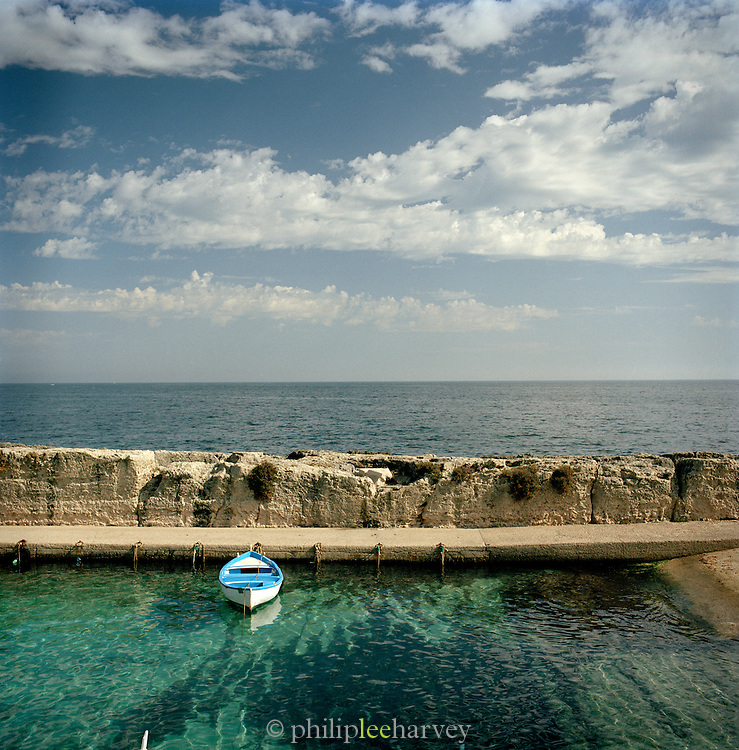 A wooden rowing boat moored in a small harbour in Castro, Puglia, Italy