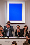 The winning bid comes over the phone via the woman to the right. Sotheby's sale of post-war and contemporary art - highlights include: a group of works from an Important Swedish Private Collection, including Lucio Fontana's rarely seen masterwork, Concetto Spaziale, Attese (1965) Estimate £5,000,000 — 7,000,000, and Robert Rauschenberg's Untitled (Small oil on canvas #4) (1963) Estimate £800,000 — 1,200,000; s a self- portrait diptych by Francis Bacon from 1977 Estimate £13,000,000 — 18,000,000; a monumental and mesmeric Abstraktes Bild by Gerhard Richter Estimate £14,000,000 — 20,000,000; and works by Cy Twombly, Nicolas de Staël, Yves Klein (pictured Blue), Jean-Michel Basquiat and Andy Warhol.