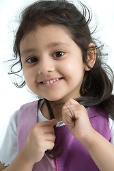 Young girl playing with her hair; smiling,