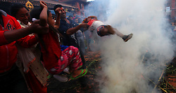 July 21, 2017 - Bhaktapur, Nepal - People kept their kids above the flame of buring effigy in belief of removing evil spirits  during the celebration of Ghantakarna festival in Bhaktapur, Nepal. Ghantakarna festival is celebrated in defeat of demon Ghantakarna chasing the evil spirits and bringing the good fortunes. (Credit Image: © Archana Shrestha/Pacific Press via ZUMA Wire)